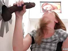 Kiki Daire pushes large black dick in glory hole inside her anus.